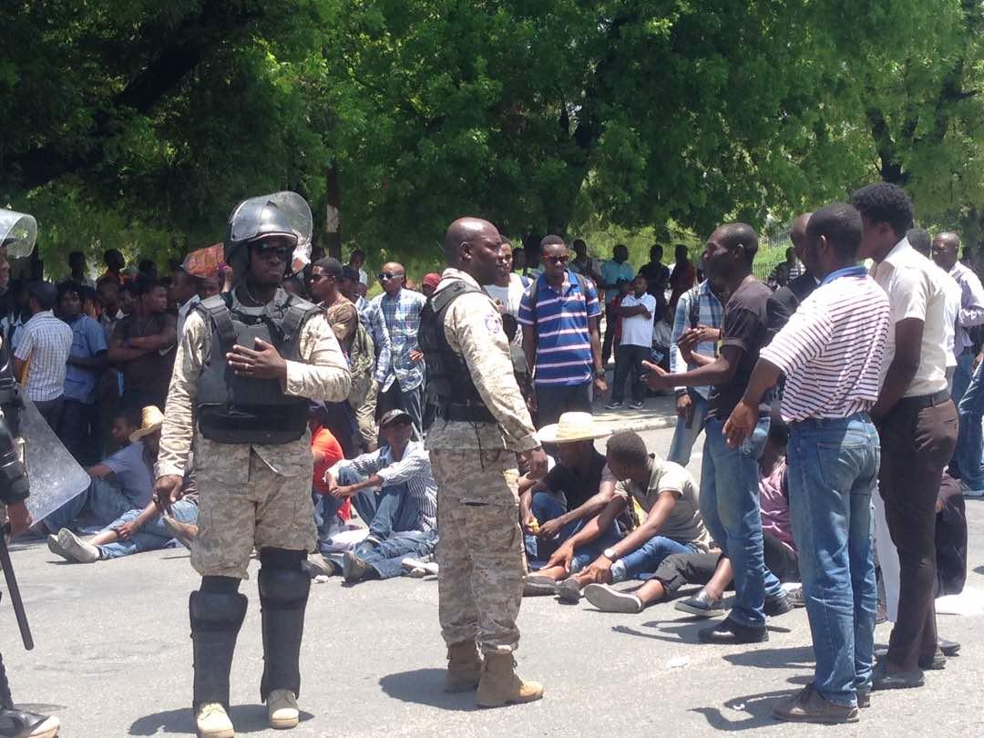 des étudiants assis devant le palais national sous l'œil vigilant de la police