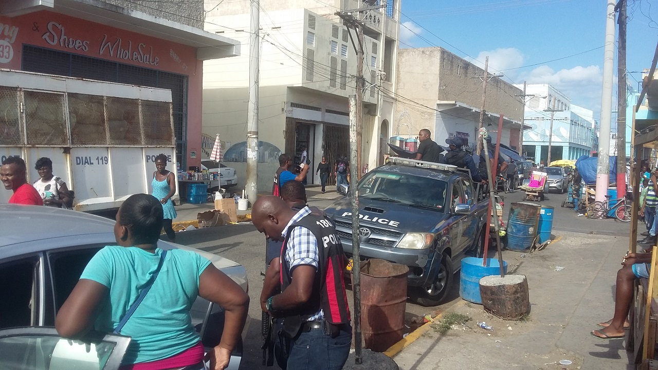 Police personnel and vehicles outside premises on Barry Street in downtown Kingston on Monday during a raid by C-TOC operatives in search of counterfeit goods.