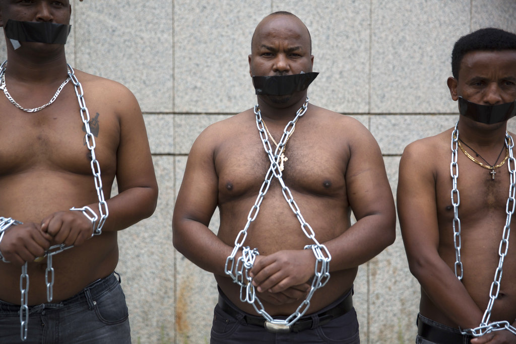 African migrants wear chains to represent slavery, during a demonstration in Tel Aviv, Israel. (AP Photo/Sebastian Scheiner)