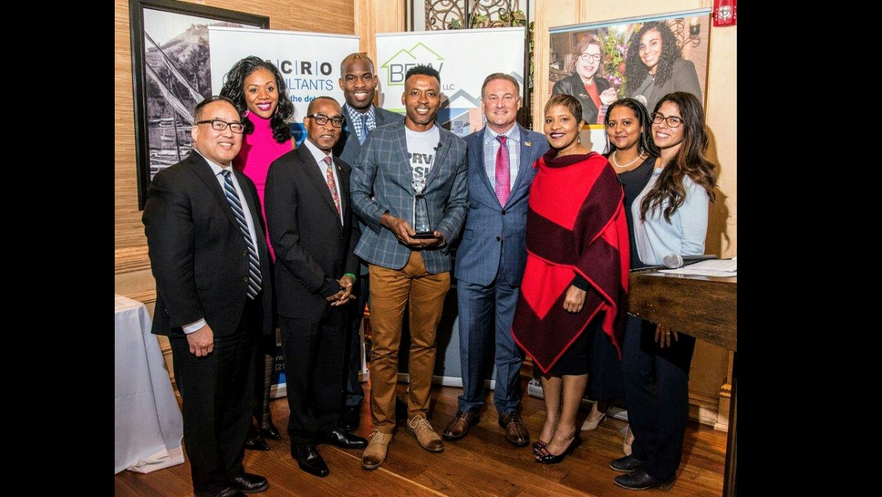 Dr Kingsley Chin (centre) - pictured with members of the Young Caribbean Professional Network - poses with the YCPN International Entrepreneur of the Year Award.