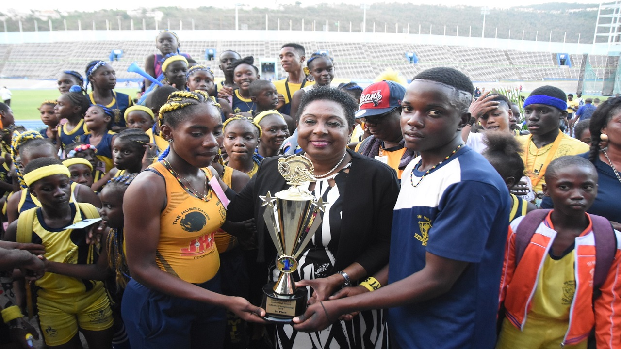 Sport Minister Olivia Grange (centre) presents members from John Mills Junior High with the championship trophy for winning the 40th and final staging of the INSPORTS All-Age & Junior High Athletics Championships at the National Stadium, on Thursday.