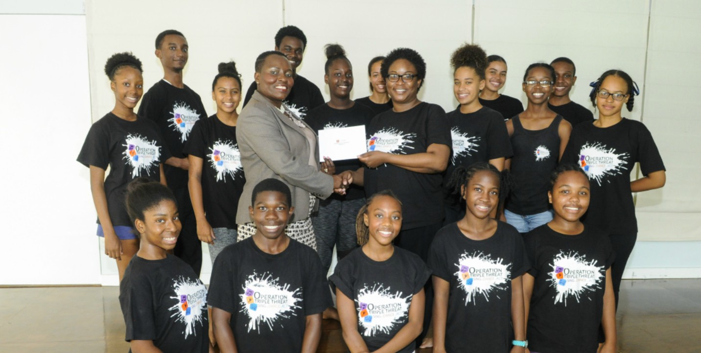 Michelle Whitelaw, CIBC FirstCaribbean's Director of Retail Banking Channels (centre left) making a presentation to Janelle Headley OTT's Founder and Director (centre right) surrounded by students of OTT.