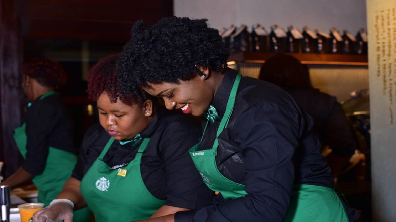 Workers prepare Starbucks coffee for guests at the grand opening of Starbucks in Montego Bay last year. Photo via Starbucks Jamaica, Facebook.