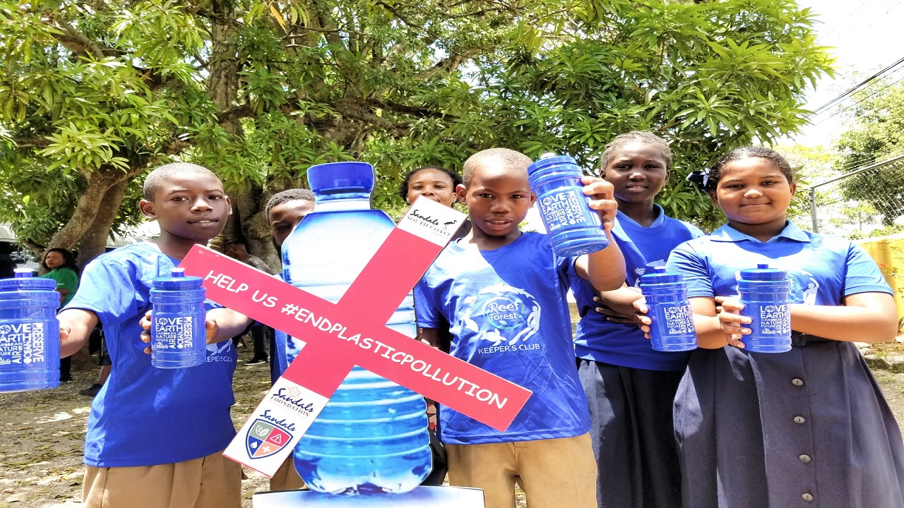 Students of Ferris Primary School showcase brand new reusable water bottles they received from Sandals South Coast Environmental Guardians who visited their school last week.