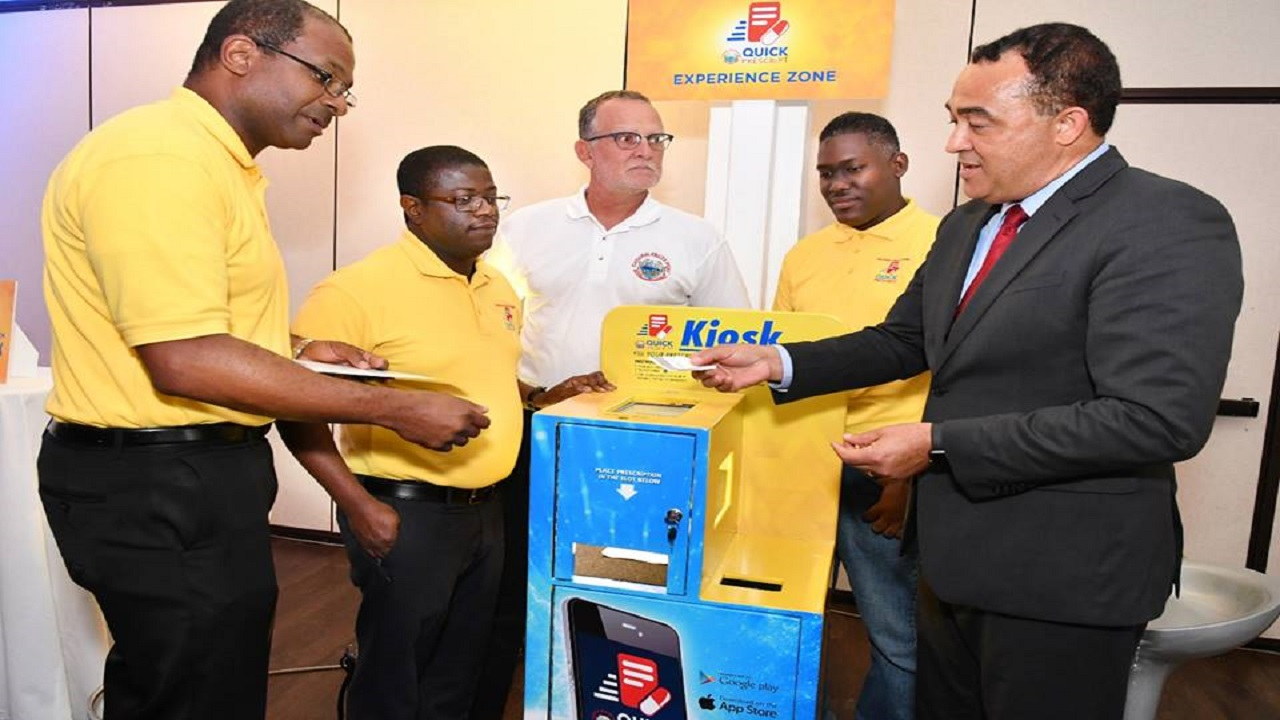 Dr Christopher Tufton, (right) Minister of Health participates in a demonstration of the National Health Fund's Quick Prescript kiosk with (from left) Granville Gayle, Senior Vice President, Information and Communications Technology, NHF; Everton Anderson, CEO, NHF; Gregory Mair, Chairman of the NHF and Dior Otto, External Applications Developer.