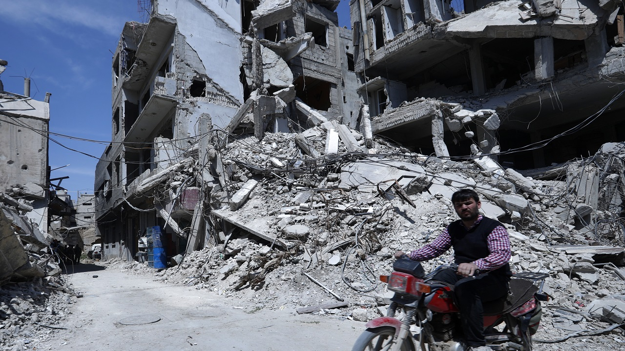 (Image: AP: A man rides past destruction in Douma, the site of a suspected chemical weapons attack, in Syria on 16 April 2018)