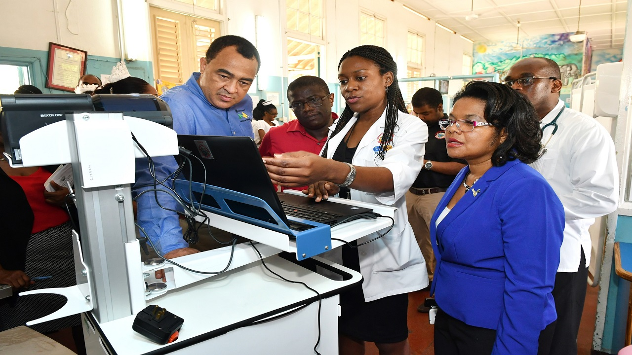 Dr. Amanda Daley (centre), Clinical Pharmacist, NHF Drug Serv,  Bustamante Hospital for Children demonstrates the Mobile Dispensing Unit, while Dr. Christopher Tufton (left), Minister of Health; Everton Anderson (second left). CEO, NHF, Dr. Michelle-Ann Richards-Dawson (right), Senior Medical Officer, BHC and Dr. Noel McLennon (back row), Consultant Paediatric Surgeon, BHC look on.