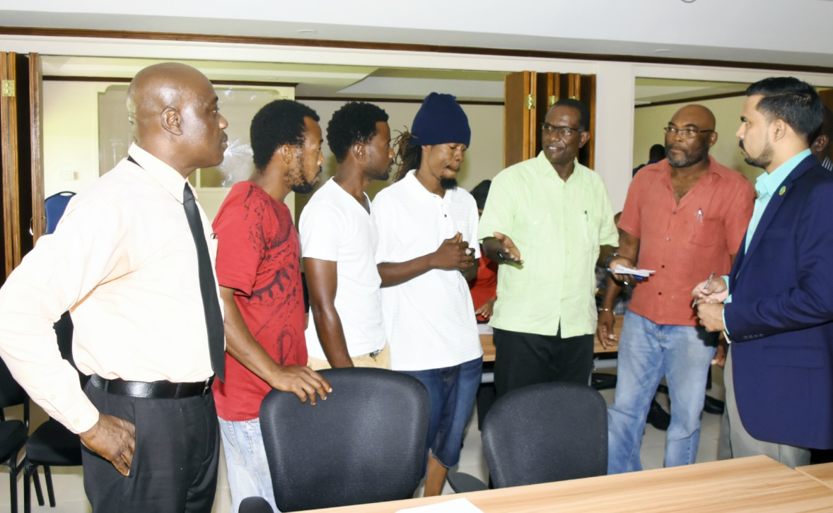Senior Environmental Health Officer, Richard Bourne (left) and coconut vendors engaged in discussion with Deputy Chief Agricultural Officer, Leslie Brereton, Deputy Chairman of the National Coconut Stakeholders' Platform, Patrice Stoute and CARDI's Local Representative, Ansari Hosein.