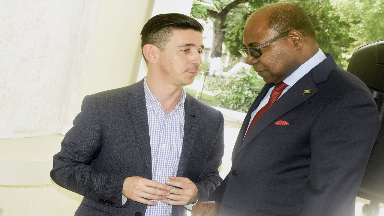 Tourism Minister Edmund Bartlett shares a word with Carlos Muñoz, Airbnb's head of public policy, Central America and the Caribbean (right). (Photos: Marlon Reid)