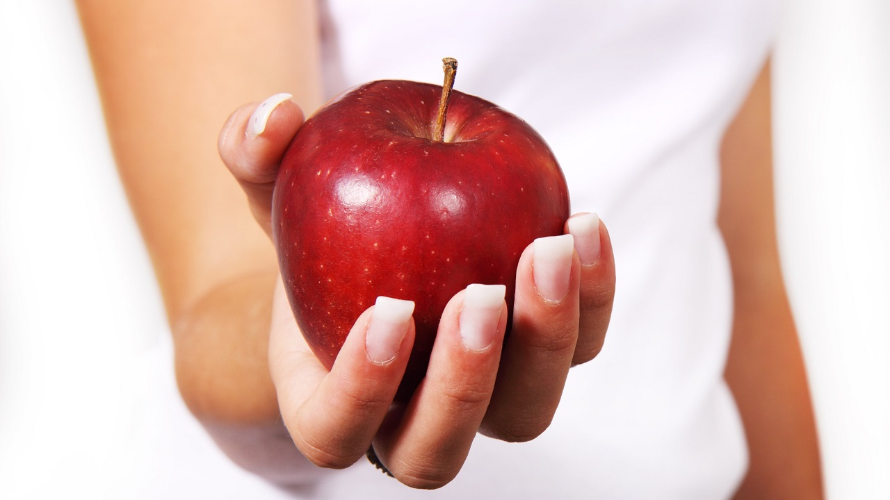(Image: File photo of a woman holding an apple via Pexels)