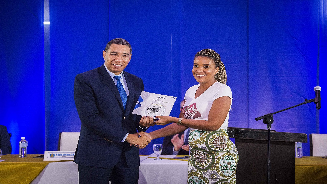 Prime Minister Andrew Holness presenting Racquell Brown, Irie Rock Yaad Spa with an award for Top Sales in the IGNITE 2017 program. (Photo: Panmedia)