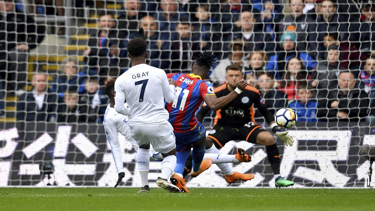 Crystal Palace's Wilfried Zaha, center, scores his side's first goal of the game during their English Premier League football match against Leicester City at Selhurst Park, London, Saturday, April 28, 2018.