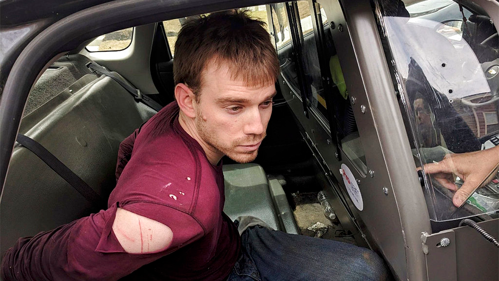 In this photo released by the Metro Nashville Police Department, Travis Reinking sits in a police car after being arrested in Nashville, Tenn., on Monday, April 23, 2018. (Metro Nashville Police Department via AP)