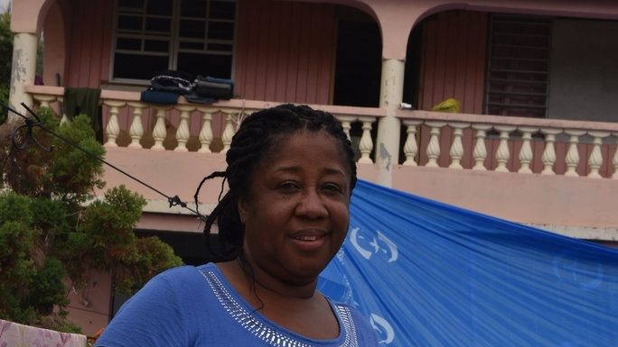 Lorna Dubique stands proudly in front of her house with a newly renovated roof.