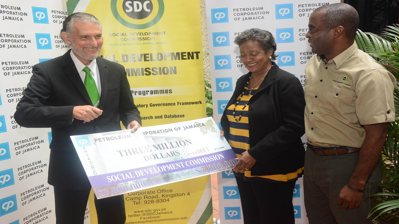 Chairman of the Social Development Commission (SDC) Prudence Kidd-Deans (centre) receives a symbolic sponsorship cheque valued at $3 million from Chairman of the Petroleum Corporation of Jamaica (PCJ) Russell Hadeed  (left) for the 2018 National Community Cricket Competition. At right is SDC's Executive Director, Dr Dwayne Vernon. The PCJ's sponsorship was handed over during a courtesy visit at the Corporation's head office in New Kingston on Wednesday, April 11, 2018.