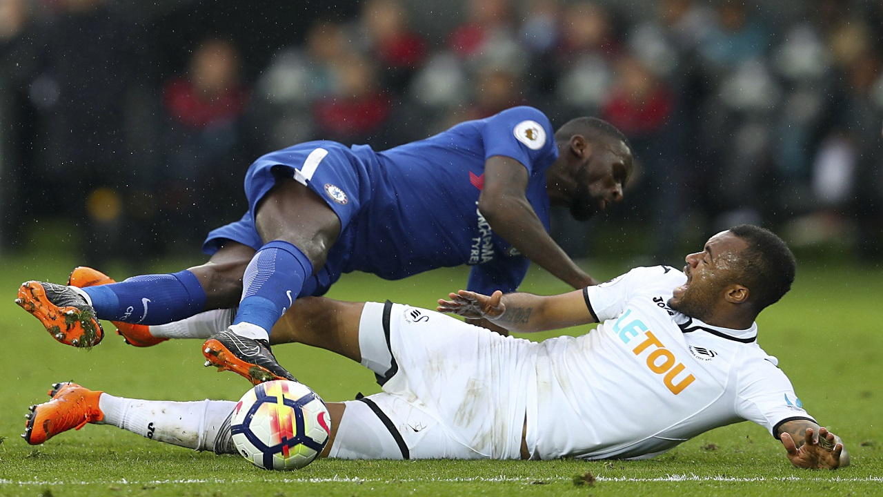 Chelsea's Antonio Rudiger, top, and Swansea City's Jordan Ayew battle for the ball during their English Premier League football match at the Liberty Stadium, Swansea, Wales, Saturday, April 28, 2018.