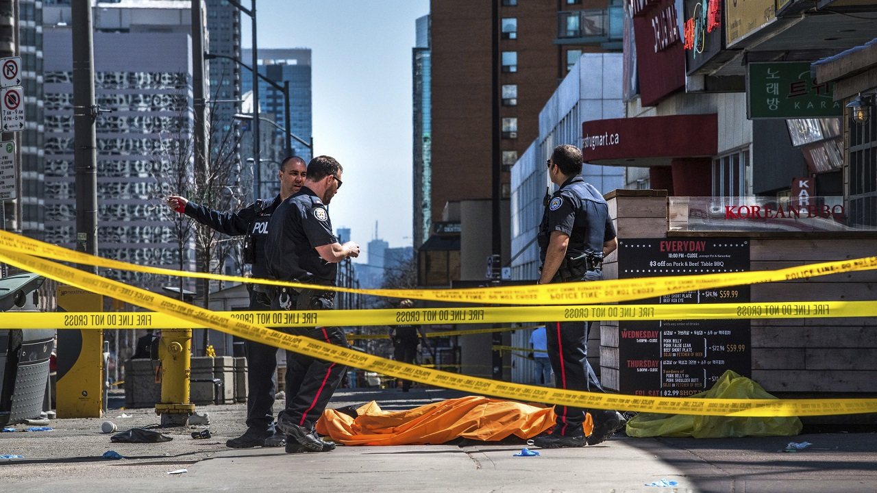 (Image: AP: Police officers stand by a covered body in Toronto after the incident on 23 April 2018)