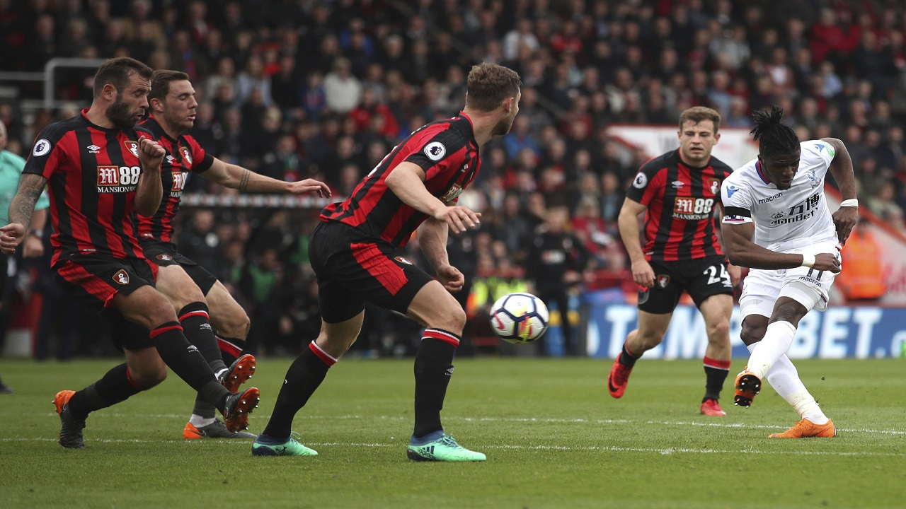 Crystal Palace's Wilfried Zaha, right, scores his side's second goal of the game during the English Premier League football match against Bournemouth at the Vitality Stadium, Bournemouth, England. Saturday, April 7, 2018.