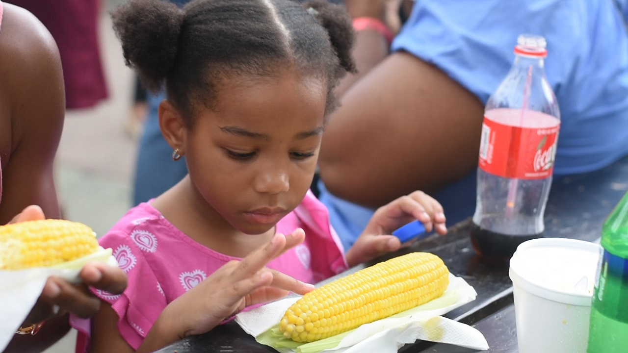 A young girl enjoys boiled corn at the CB Food Court at the Expo Jamaica on Sunday.