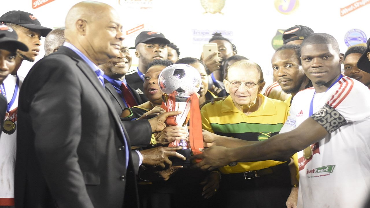 Portmore United captain Ewan Grandison (right) receives the Red Stripe Premier League trophy during the presentation ceremony at the National Stadium on Monday night. Also in the presentation party are President of the Jamaica Football Federation Michael Ricketts (left); Sports Minister Olivia Grange (partly hidden, 2nd left) and Edward Seaga (2nd right), Chairman of the Premier League Clubs Association and a former Prime Minister of Jamaica. (PHOTO: Marlon Reid).