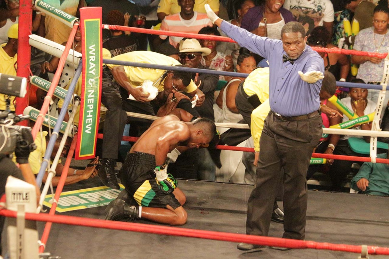 The referee waves off the fight with Jamaican Gregory Miller on his knees after he was knocked to the canvas by Canadian Francesco Cotroni in the third round of their 2017 Wray and Nephew Contender Boxing Series bout on Wednesday night at the Chinese Benevolent Association.
