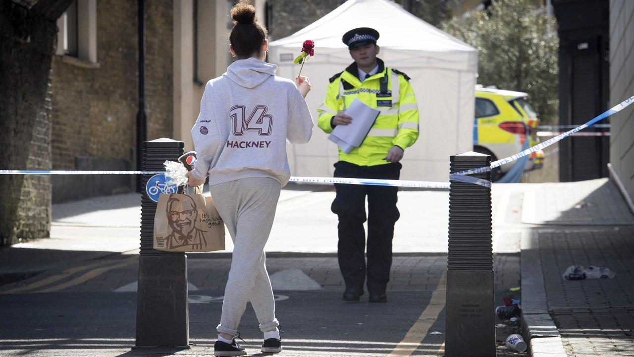 (Image: AP: A woman carries a flower to a crime scene in east London on 5 April 2018)