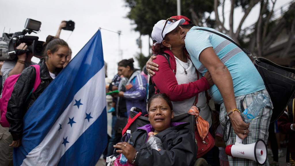 Central Americans who travel with a caravan of migrants embrace in Tijuana, Mexico, before crossing the border and request asylum in the United States. A group of Central Americans who journeyed in a caravan to the U.S. border resolved to turn themselves in and ask for asylum Sunday in a direct challenge to the Trump administration - only to have U.S. immigration officials announce that the San Diego crossing was already at capacity.