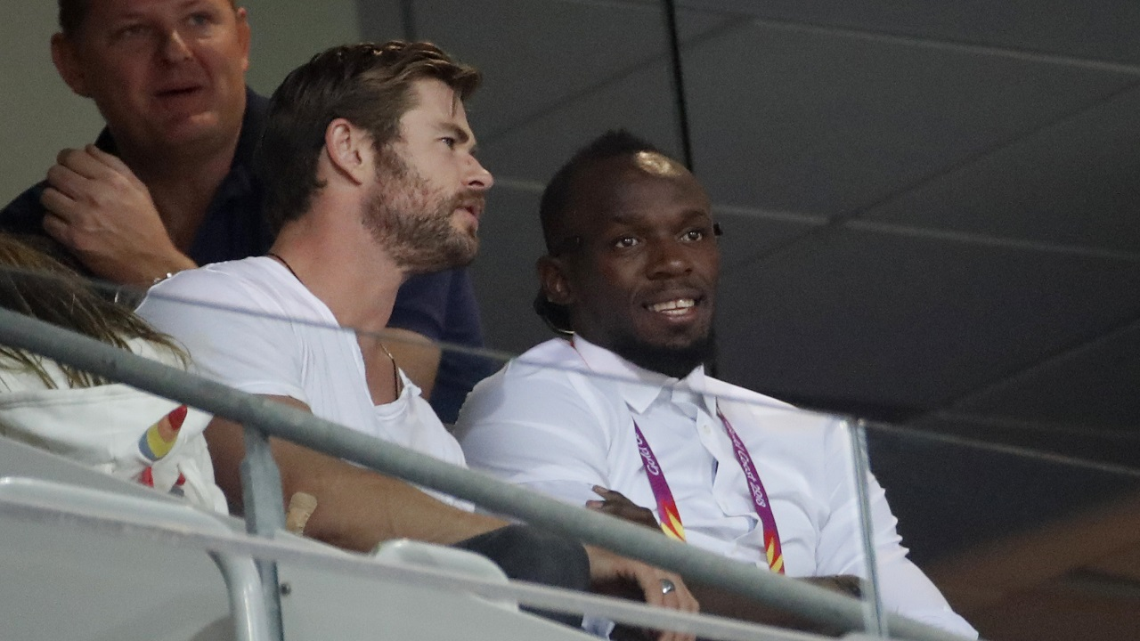 (Image: AP: Hemsworth and Bolt watch the Commonwealth Games on 12 April 2018)