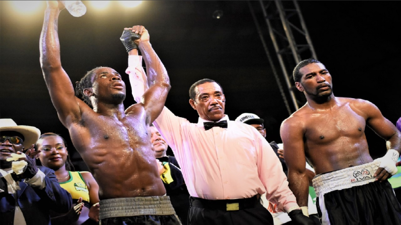 Referee Eion Jardine raises the left arm of Jamaican Richard 'Frog' Holmes after he was declared  winner of the opening bout of the 2018 Contender Series on Wednesday night, at the Chinese Benevolent Association auditorium. Holmes scored a unanimous decision victory  over Canadian Lloyd Reyes. (PHOTO: Marlon Reid).