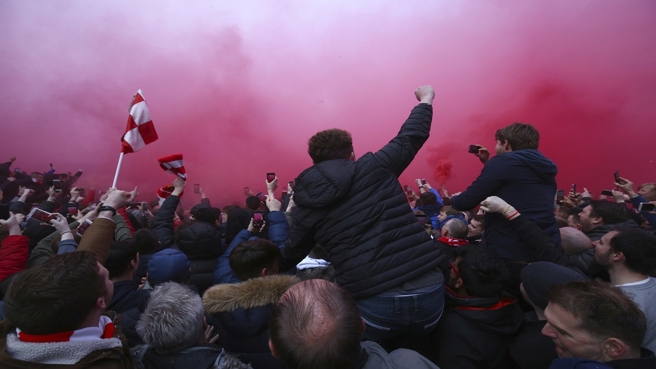 A flare burns as football fans try to see the Manchester City team bus as it arrives ahead of the Champions League quarter final first leg football match against Liverpool  at Anfield stadium in Liverpool, England, Wednesday, April 4, 2018.
