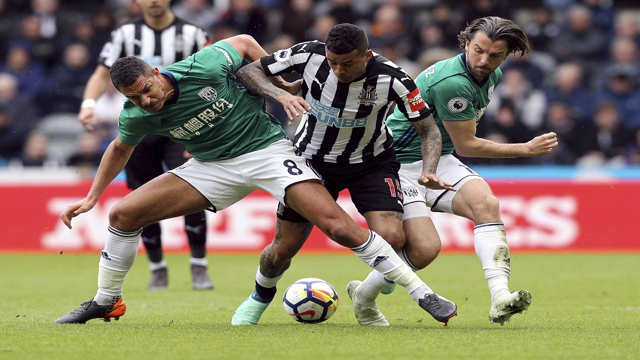Newcastle United's Kenedy, centre, battles for the ball with West Bromwich Albion's Jake Livermore, left and Jay Rodriguez during their English Premier League football match at St James' Park, in Newcastle, England, Saturday April 28, 2018.