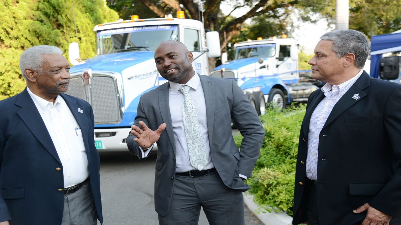 Andrew Wheatley, Minister of Science, Energy and Technology (centre) discusses the benefits of the usage of liquified natural gas (LNG) with Wayne Kirkpatrick (right) General Manager, IGL Ltd. and Bevon Francis, Board Chairman, IGL, at the company's launch for its new LNG-powered tractor heads on Wednesday.