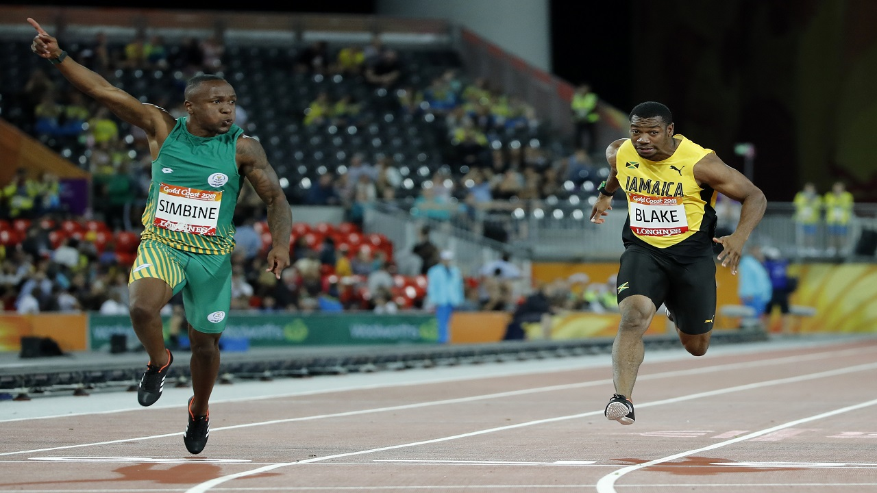 South Africa's Akani Simbine, left, celebrates after winning the men's 100m final at Carrara Stadium during the 2018 Commonwealth Games on the Gold Coast, Australia, Monday, April 9, 2018. Jamaica's Yohan Blake, right, finished third.