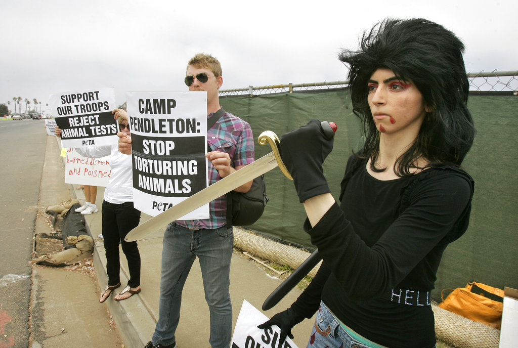 This file photo shows Nasim Aghdam, right, as she joins members of People for the Ethical for Animals, PETA, protesting at the main gate of Marine Corps base Camp Pendleton in Oceanside, California. (Charlie Neuman/The San Diego Union-Tribune via AP)