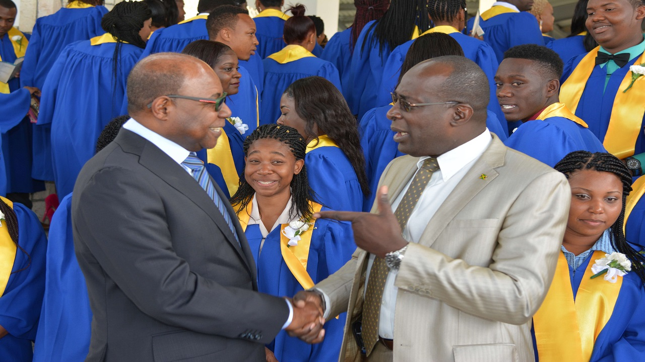 Tourism Minister Edmund Bartlett (left) with Education Minister Ruel Reid at the graduation of over 150 hospitality workers.