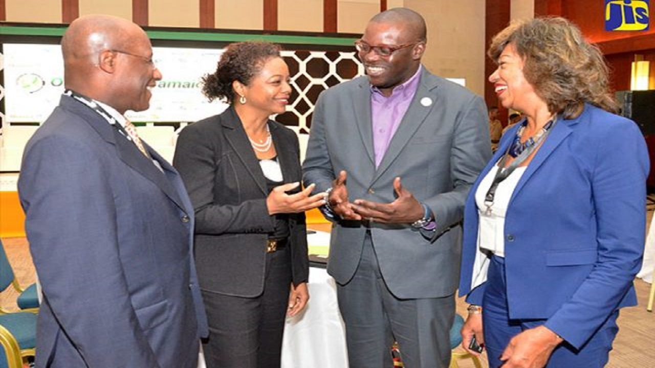 Attorney General, Marlene Malahoo Forte (second left), shares in discussion with (from left) Executive Director of the Economic Growth Council, Senator Aubyn Hill; Managing Director of Flow Jamaica, Stephen Price; and President of JAMPRO, Diane Edwards. The occasion was the opening of the inaugural Outsource2Jamaica Symposium and Expo at the Montego Bay Convention Centre in St James on April 12.