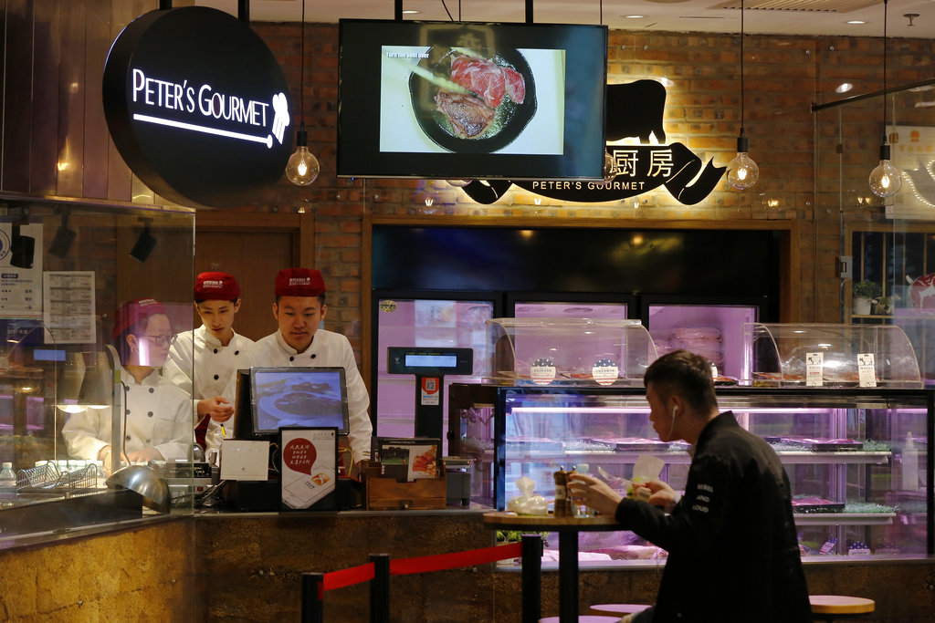 A man eats at a restaurant serving imported American beefs at a shopping mall in Beijing. (AP Photo/Andy Wong)
