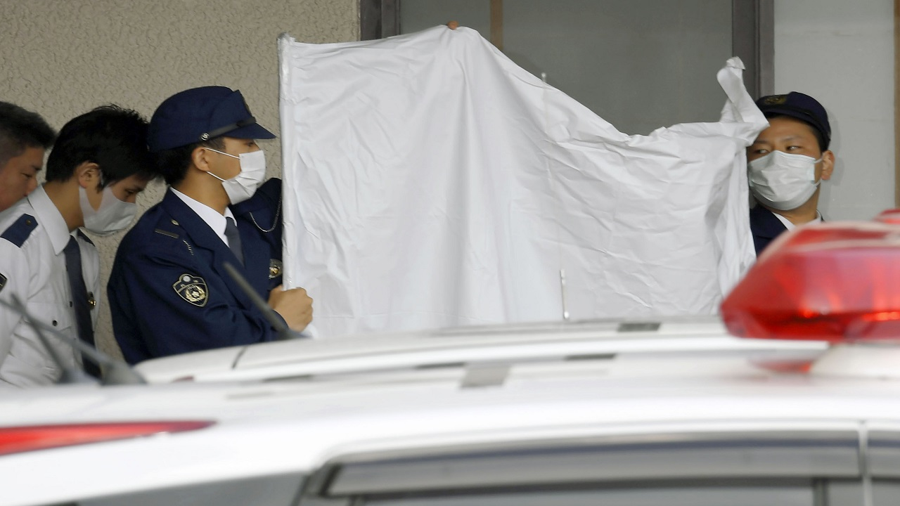 (Image: AP: Police conceal Yoshitane Yamasaki as he meets prosecutors in Japan on 9 April 2018)