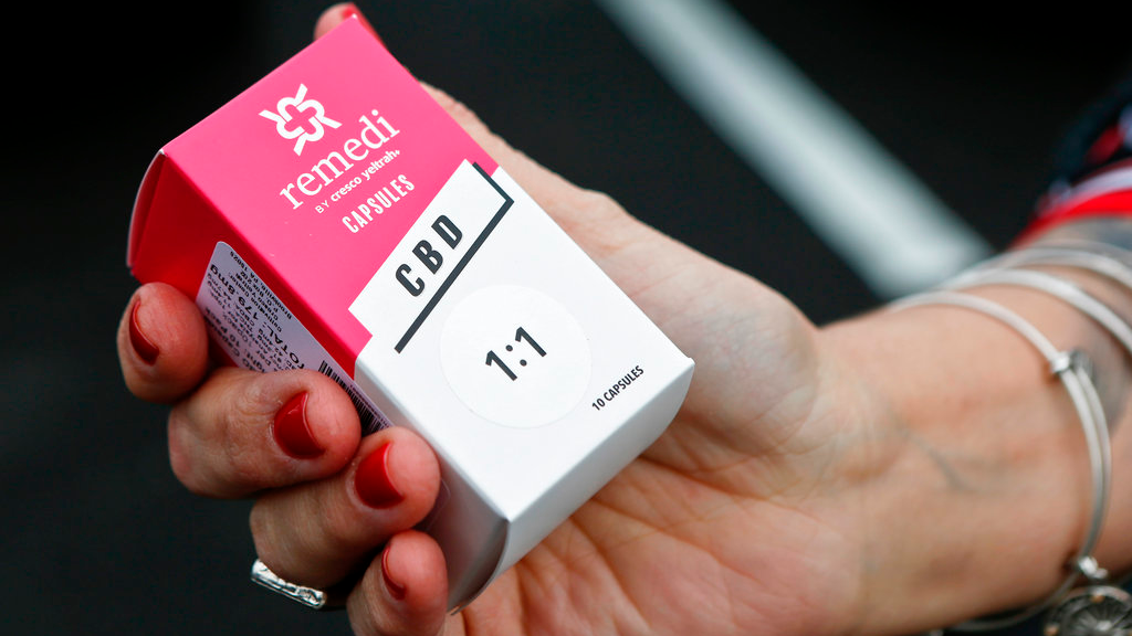 In this Thursday, Feb. 15, 2018 file photo, a woman holds the prescribed medical marijuana product used to treat her daughter's epilepsy after making a purchase at a medical marijuana dispensary in Butler, Pa. Two new studies released on Monday, April 2, 2018 suggest that legalization of marijuana may reduce the prescribing of opioids. (AP Photo/Keith Srakocic)