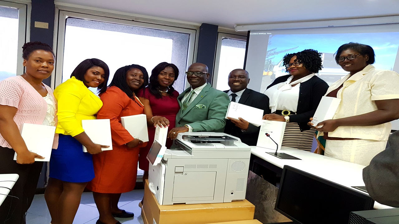 Local Government and Community Development Minister, Desmond McKenzie (centre), and members of the St James Municipal Corporation pose with new tablets and a printer on Thursday.