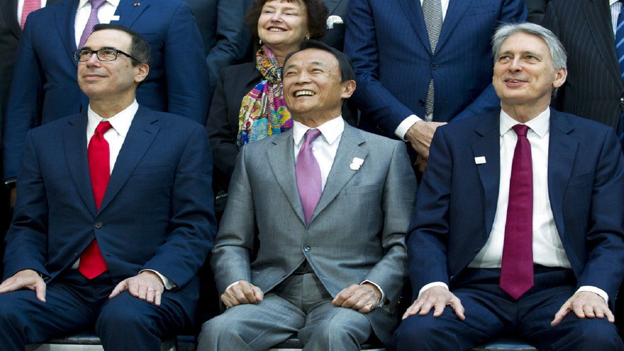 (Foreground from left) U.S. Treasury Secretary Steve Mnuchin, Japan's Finance Minister Taro Aso and U.K. Chancellor of the Exchequer Philip Hammond sit with others for the group photo of International Monetary Fund governors at the World Bank/IMF Spring Meetings in Washington.