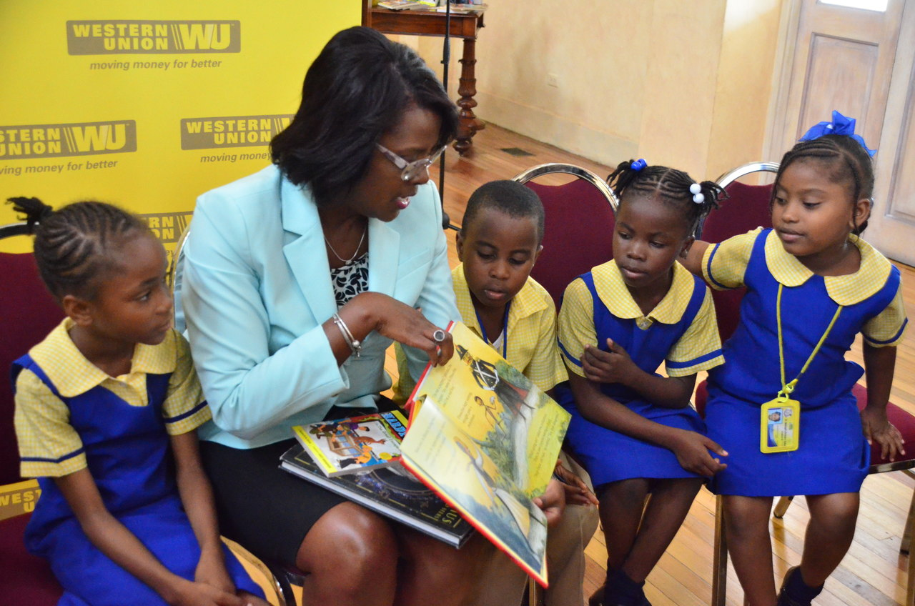 Michelle Allen, CEO of GKMS reads to students in Kingston during the I-PLEDGE launch.