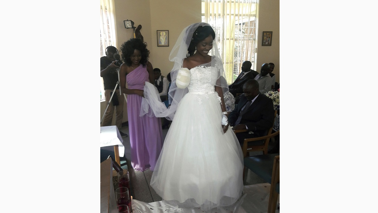 (Image: AP: Zenele Ndlovu walks down the aisle on her wedding day at a hospital Chapel in Bulawayo, Zimbabwe on 5 May 2018)