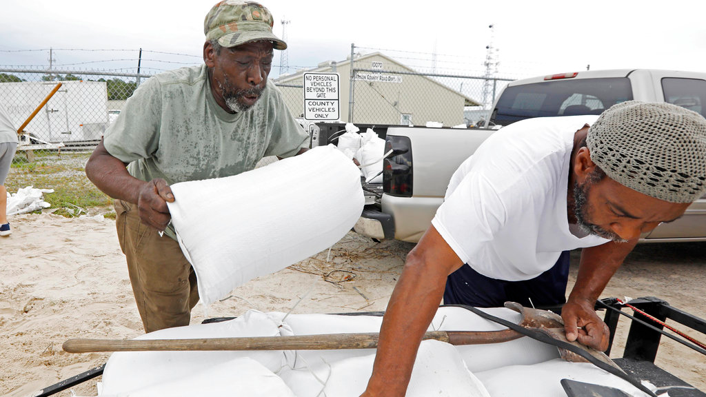 Tommy Whitlock, left, places a filled sand bag onto his trailer at a Harrison County Road Department sand bag location, as his friend Joseph Buckner adjusts the load while preparing for Subtropical Storm Alberto to make its way through the Gulf of Mexico in Gulfport, Miss., Saturday, May 26, 2018. (AP Photo/Rogelio V. Solis)