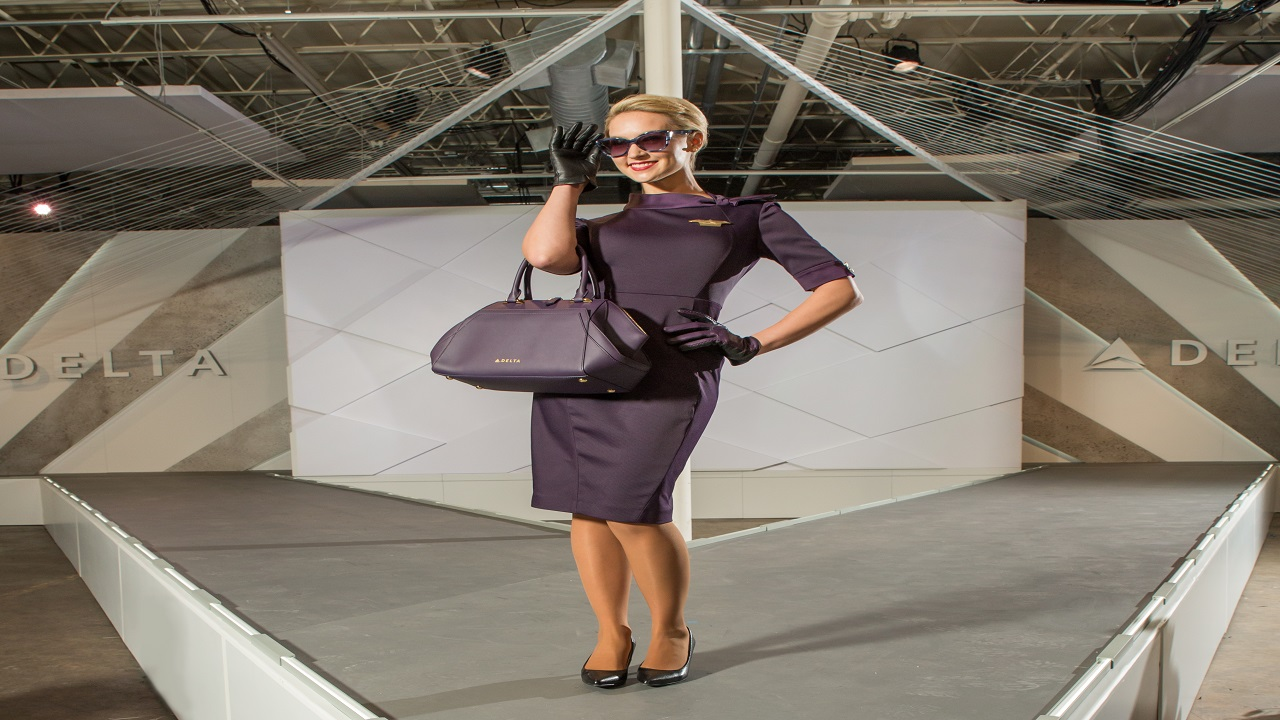 In flight service signature passport plum dress with matching leather glove and handbag.  Photo via Delta News Hub.
