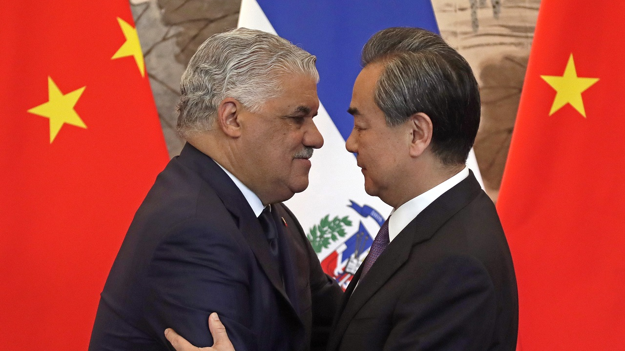 (Image: AP: Dominican Foreign Minister Miguel Vargas hugs Chinese Foreign Minister Wang Yi after signing the communique in Beijing on 1 May 2018)
