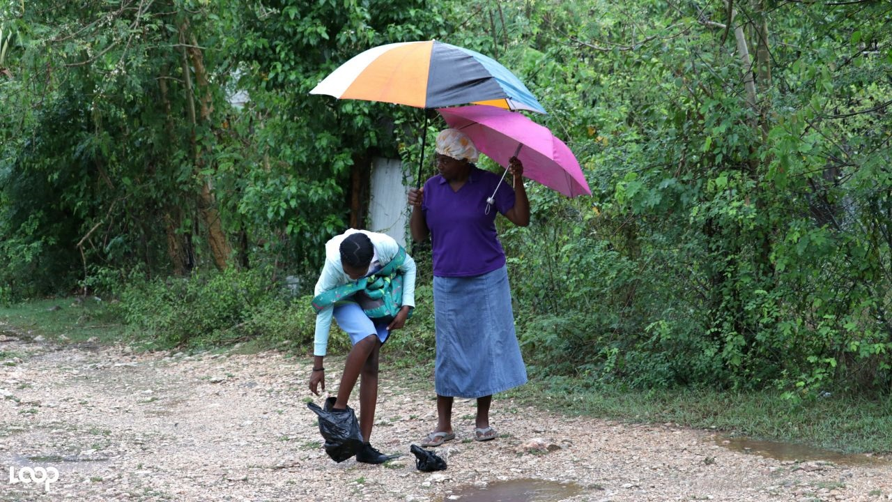 A girl ties plastic bags on her shoes while a woman looks on attentively amid rainfall in Seven Heights , Clarendon on Monday morning. (PHOTOS: Shawn Barnes)