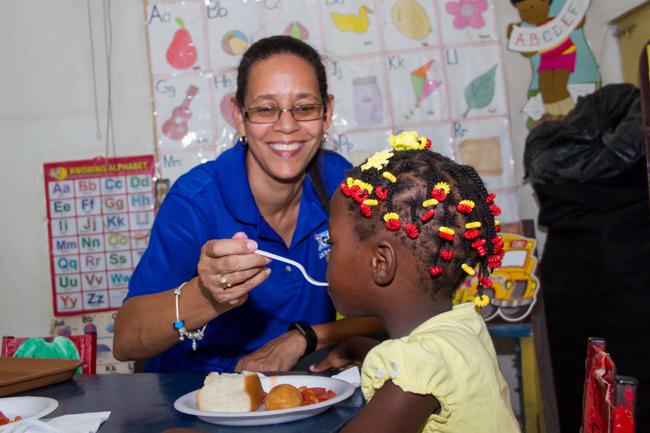 Annakaye Tucker, IGL Trade Marketing Manager feeds breakfast to a student of the Riverton Meadows Early Childhood Centre at the Ignite IGL Foundation Annual Breakfast Feeding Program on Children's Day, May 18, 2018.
