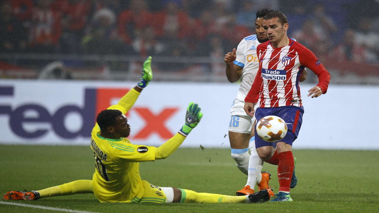 Atletico's Antoine Griezmann scores against Marseille's goalkeeper Steve Mandand in the Europa League final at the Stade de Lyon in Decines, outside Lyon, France, Wednesday, May 16, 2018.