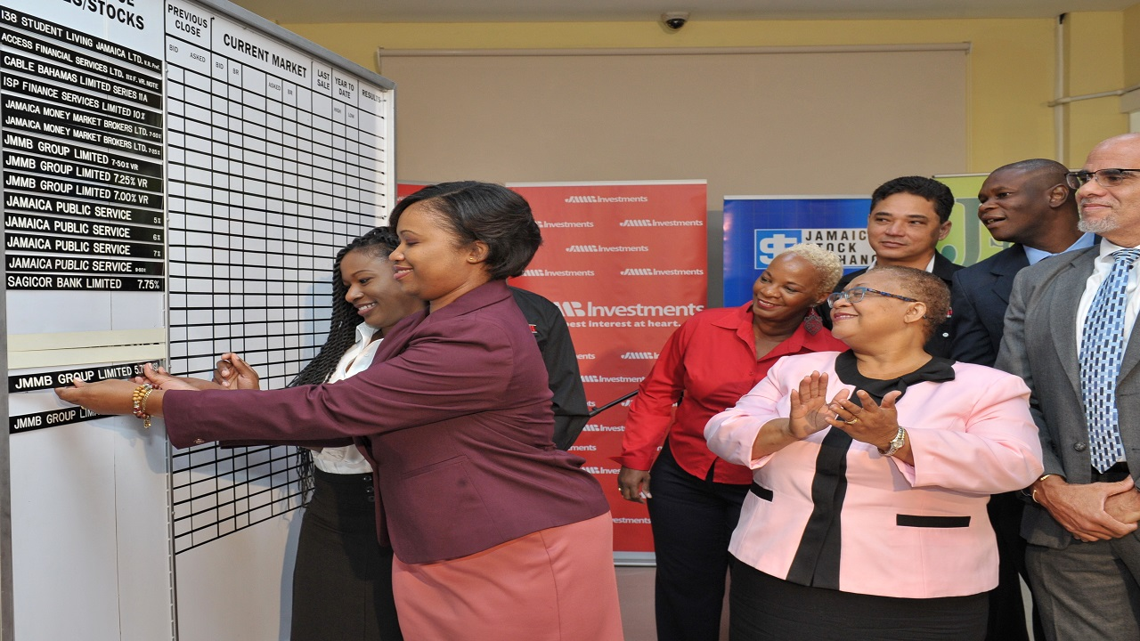 JMMB's Marsha-Gaye Hibbert and Rashida Hall (left) skillfully inserts the strip for one of the Preference Share, Fixed Rate during the JMMB Group's listing ceremony. Looking on are: Marlene Street-Forrest (centre), managing director, JSE and Keith Duncan (right, front row), CEO, JMMB Group and (second left to right, back row), Archibald Campbell (partially hidden) JMMB Group chairman, the company's directors, Anne Crick and Reece Kong and JSE's Neville Ellis.